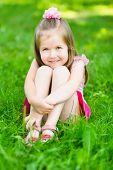 stock photo of bow-legged  - Cute little girl with long blond hair sitting on grass in summer park putting her hands around her legs outdoor portrait - JPG