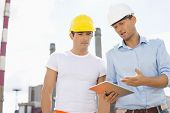 stock photo of headgear  - Male construction workers discussing over digital tablet at industry - JPG