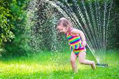 picture of sprinkler  - Funny laughing little girl in a colorful swimming suit running though garden sprinkler playing with water splashes having fun in the backyard on a sunny hot summer vacation day - JPG