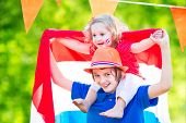 image of holland flag  - Two Dutch children teenager boy and funny little girl celebrating national holiday of Netherlands playing in a garden decorated with Holland and Oranje flags - JPG