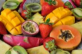 stock photo of fruit platter  - Tropical fruit sliced and arranged on a wooden cutting board - JPG