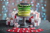 picture of cake stand  - Nice sponge happy birthday cake with mascarpone and grapes with on the cake stand with gift boxes on festive light bokeh background - JPG