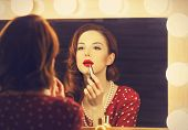 stock photo of mirror  - Portrait of a beautiful woman as applying makeup near a mirror - JPG