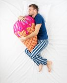 foto of sweet dreams  - Top view photo of young man sleeping in an embrace with a large soft ice cream toy and dreaming of sweets - JPG