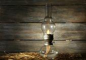 image of kerosene lamp  - Kerosene lamp with hay on rustic wooden planks background - JPG