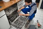stock photo of sanitation  - Portrait Of Male Technician Repairing Dishwasher In Kitchen