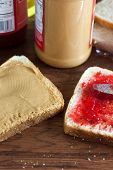 picture of jar jelly  - A peanut butter and jelly sandwich being constructed on a wooden table - JPG