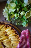 stock photo of helleborus  - French apple tart on the old rustic table with flowers and napkin - JPG