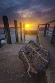 picture of lobster trap  - The sun goes down over a lone lobster pot by a slipway  - JPG