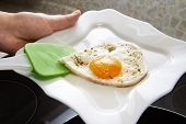 image of yoke  - Cook puts fried eggs in the form of heart on a white plate - JPG