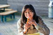 picture of biracial  - Young biracial teen girl outdoors eating hamburger - JPG