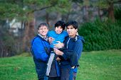 foto of biracial  - Disabled biracial child carried by his father and brother at park.