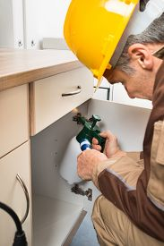 image of pesticide  - Pest Control Worker In Work wear With Flashlight And Spraying Pesticides Inside Cabinet - JPG