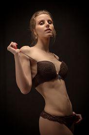 foto of strip tease  - slim muscular woman in lingerie on black background - JPG