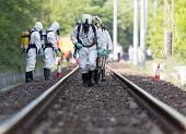 image of accident emergency  - A team working with toxic acids and chemicals is approaching a chemical cargo train crash near Sofia Bulgaria. Teams from Fire department are participating in an emergency training with spilled toxic and flammable materials.