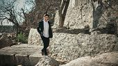 image of slab  - Fashion photo of a man on a seaside walking on the concrete slabs near the stone wall - JPG