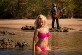 stock photo of guitarists  - blonde pretty girl in pink swimsuit sit in shallow sea against bearded guitarist play - JPG