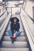 picture of escalator  - Gorgeous young brunette with hat posing on an escalator - JPG