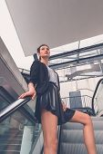 foto of mini-skirt  - Gorgeous young brunette in black skirt posing on an escalator - JPG