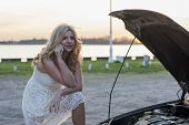stock photo of woman boots  - Blond woman wearing white lace dress and short black boots in front of the trunk of a car thinking what to do after car break down - JPG