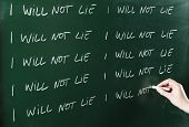 stock photo of punishment  - I will not lie sentence written repeatedly on blackboard as a punishment - JPG