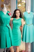 stock photo of boutique  - Stylish woman in fashion boutique among trendy gowns - JPG