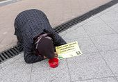 picture of begging  - An old woman is begging on the ground of a main street in Budapest Hungary - JPG