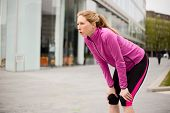 pic of breathing exercise  - a young runner catching her breath after running - JPG