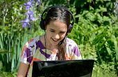 image of hispanic  - Little Hispanic girl using a computer in an urban green space - JPG