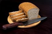 picture of whole-grain  - Whole grain brown bread on cutting board on black background - JPG