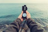 picture of pov  - Traveler woman searching direction with a compass on stone coastline near the sea - JPG