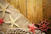 stock photo of sackcloth  - Sea stars on sackcloth on wooden background - JPG