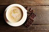 picture of latte  - Cup of coffee latte art with grains and chocolate on wooden background - JPG