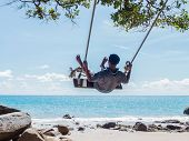 picture of swing  - Young man swinging in a swing on tropical summer beach - JPG