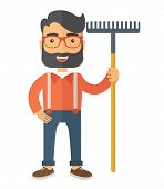 picture of headgear  - A caucasian man standing holding a rake ready for gardening - JPG