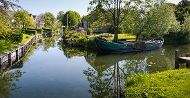 stock photo of historical ship  - Historic sailing ship in the canal of a small Dutch village in the spring season - JPG