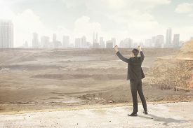 picture of corruption  - Asian business man looking at the destroyed city - JPG