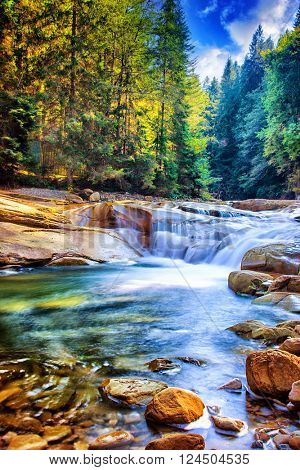 Beautiful waterfall in the forest,  fresh water flows between stones and rocks, wonderful landscape,