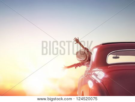 poster of Toward adventure! Girl relaxing and enjoying road trip. Happy girl rides into the sunset in vintage