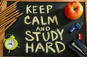 Composition with phrase Keep calm and study hard and stationery on chalkboard, top view poster
