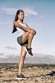 Leg stretching exercise fitness runner woman doing running warm-up, hamstring muscles stretch standi poster