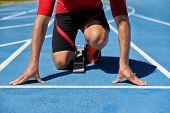 Runner athlete starting running at start of run track on blue running tracks at outdoor athletics an poster
