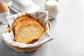 Wicker basket with tasty toasted bread on table poster