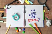 Notebook with question Are you ready for exams? and alarm clock on table poster