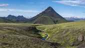 Panoramic Volcanic Landscape Of Green Storasula Mountain With Lush Moss And Blue Creek Water Between poster
