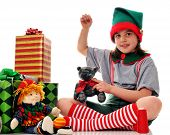 stock photo of knee-high socks  - An elf sewing a stuffed animal getting ready for Santa to deliver on Christmas eve - JPG