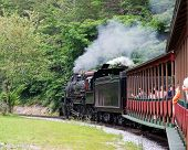 foto of old-fashioned  - A vintage steam engine leading a tour train - JPG