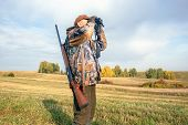 Man Hunter Outdoor In Autumn Hunting. Hunter Looking Through Binoculars. poster