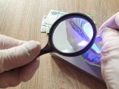 Verification Of Banknotes By An Ultraviolet Lamp For Authenticity. poster