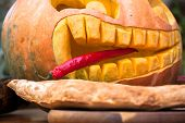 Hungry Pumpkin With Pepper. In Mouth A Pointy Red Pepper Tongue Sticks Out Between Crooked Tip Teeth poster